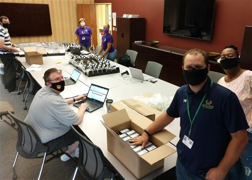 Technology team members prepare wifi hotspots for distribution to schools, for students